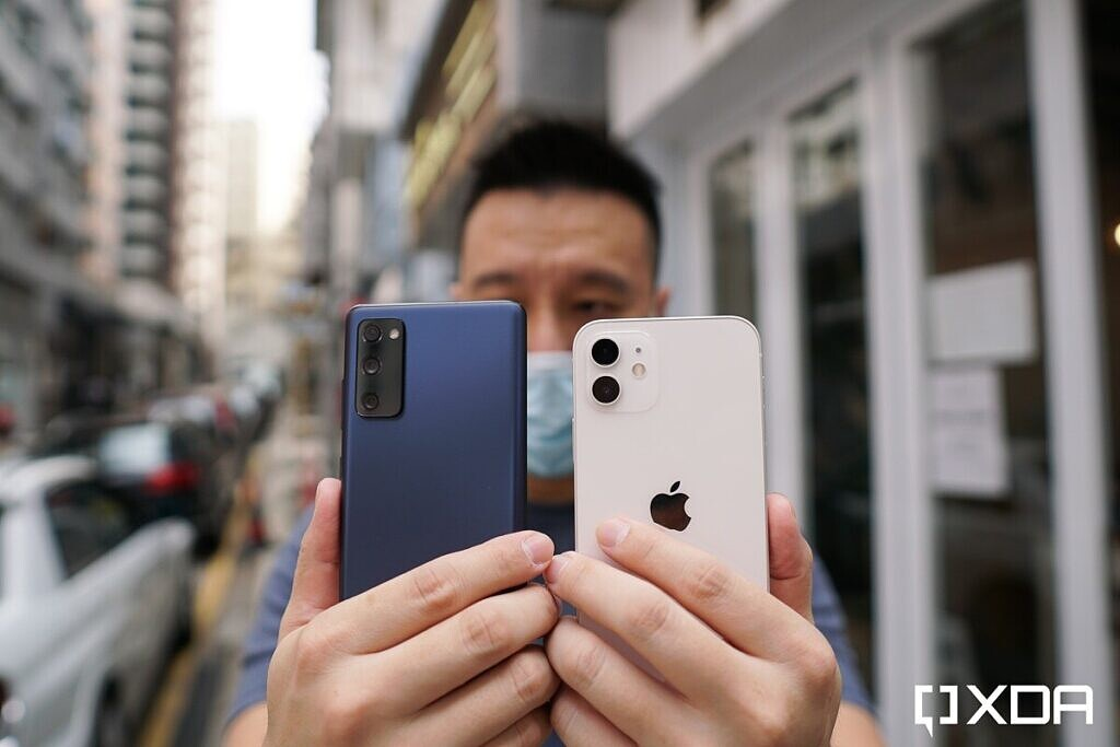 Samsung Galaxy S20 FE in blue and Apple iPhone 12 in White, both in the hand and back facing the camera