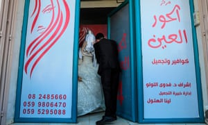 Palestinian groom Ahmed Omar Khallah picks up his veiled bride from a beauty salon in the northern Gaza Strip.