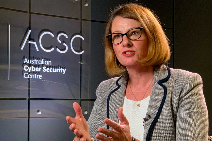 A woman sits in front of a sign for the Australian Cyber Security Centre.