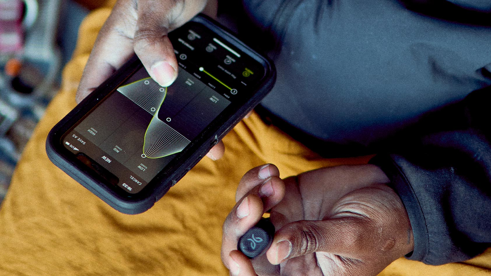 A man uses the Jaybird Vista 2 true wireless workout earbuds' mobile app to adjust the EQ.