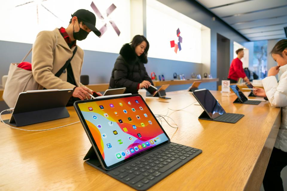 Customers admire iPad Pro products in an Apple retail store...
